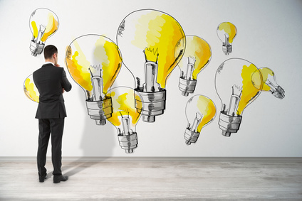Back view of thoughtful young businessman in interior looking at concrete wall with drawn yellow light bulbs. Idea and success concept